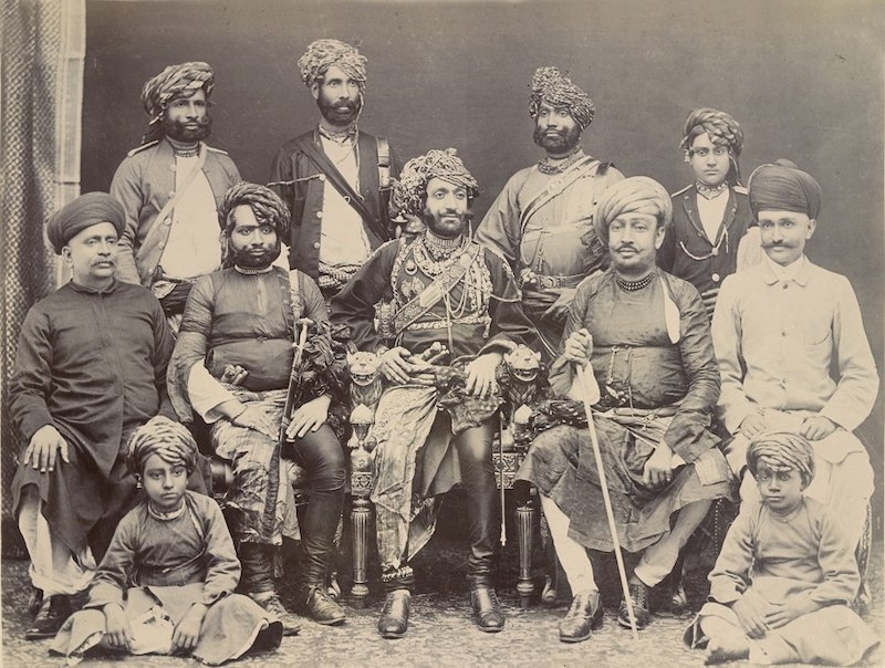 .<br />The Nawab of Junagarh, Bahadur Khan III (seated centre in an ornate chair), shown in an 1885 photograph with state officials and family.