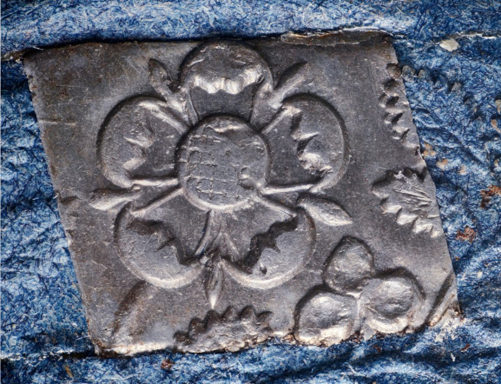 central flower in embossed escutcheon rotated